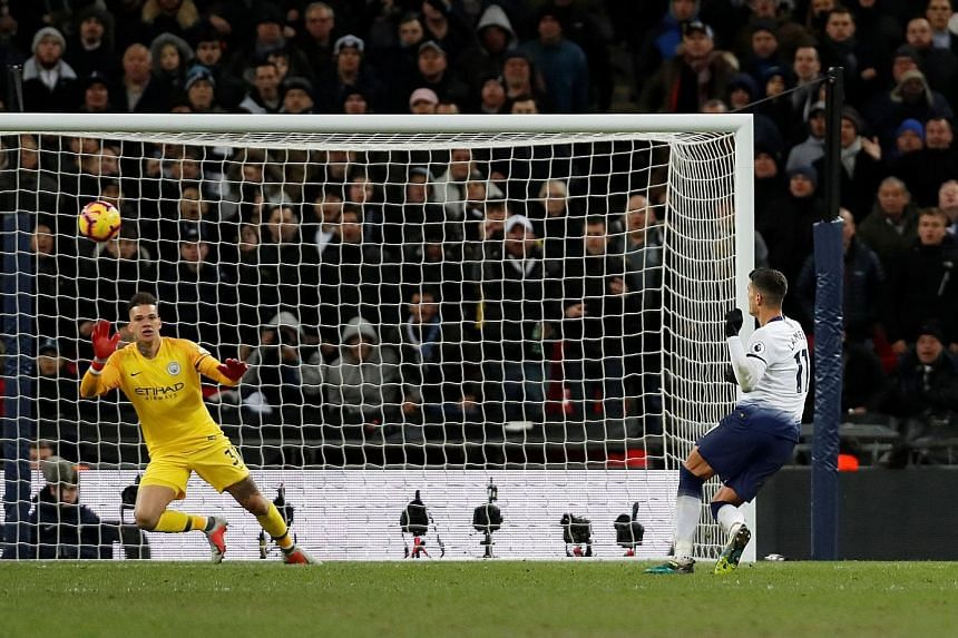 Left: Spurs' Erik Lamela missing a chance to score with this effort that went over the bar, no thanks to an uneven playing surface at Wembley, which had been used for an American football match the day before. The Londoners have delayed a move to the