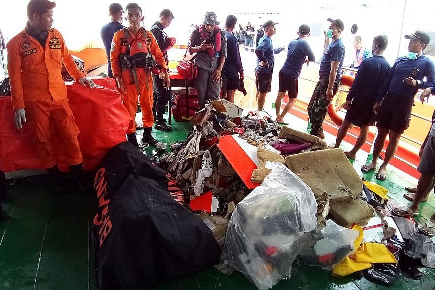 Indonesian rescuers with some items recovered yesterday from the crash site, including personal belongings and pieces of the wreckage, as well as a body. So far, rescuers have sent 34 body bags containing human remains for DNA testing.