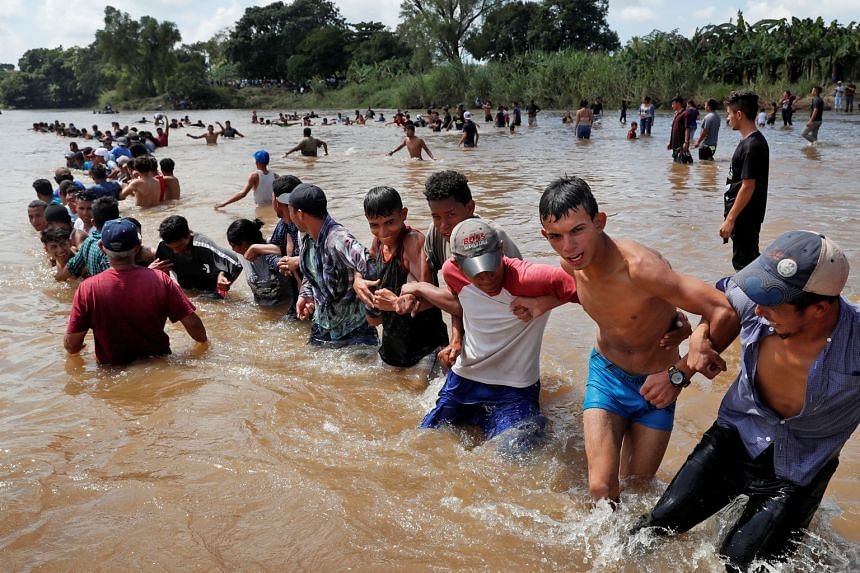 Central American migrants, part of a caravan headed for the US, forming a human chain on Monday to pull people from the river between Guatemala and Mexico before continuing on their trek to the US.