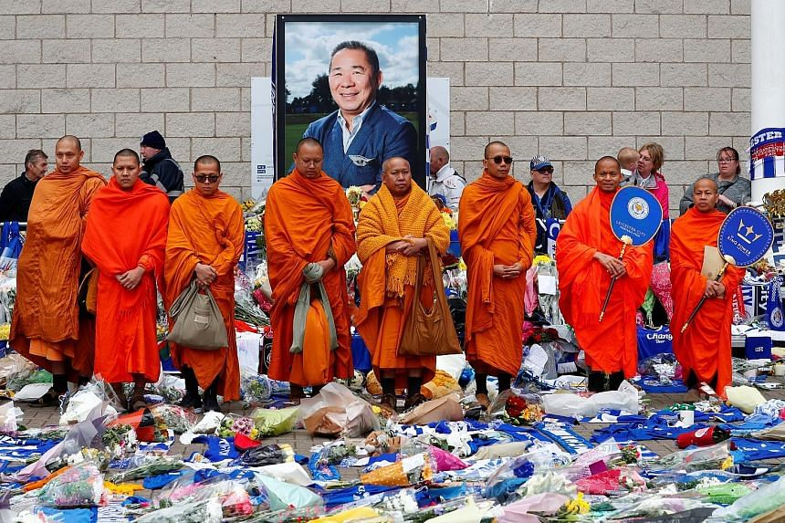 Buddhist monks standing in tribute following prayers for Leicester's late owner Vichai Srivaddhanaprabha and four others who died when their helicopter crashed as it left the ground after last Saturday's match against West Ham.