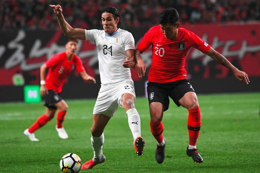 Uruguay's Edinson Cavani (in white) fights for the ball with South Korea's Jang Hyun-soo during a friendly football match in Seoul on Oct 12, 2018.