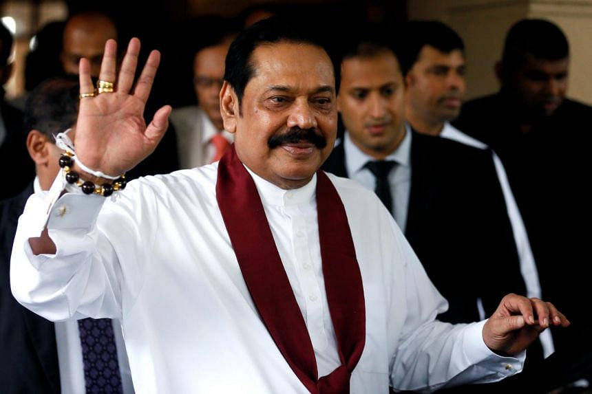 Sri Lanka's newly appointed Prime Minister Mahinda Rajapaksa waves after participating in the ceremony to assume his duties as the Minister of Finance and Economic Affairs at the Finance Ministry in Colombo, Sri Lanka, on Oct 31, 2018.