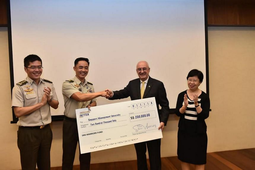 Brigadier-General Chua Boon Keat presenting a cheque for $200,000 to SMU president, Professor Arnoud De Meyer, at SMU on Nov 1, 2018. With them are Chief of Defence Force Melvyn Ong and SMU provost, Professor Lily Kong.