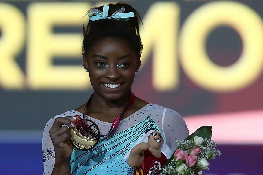 Simone Biles poses with her gold medal after winning the women's all-around final.