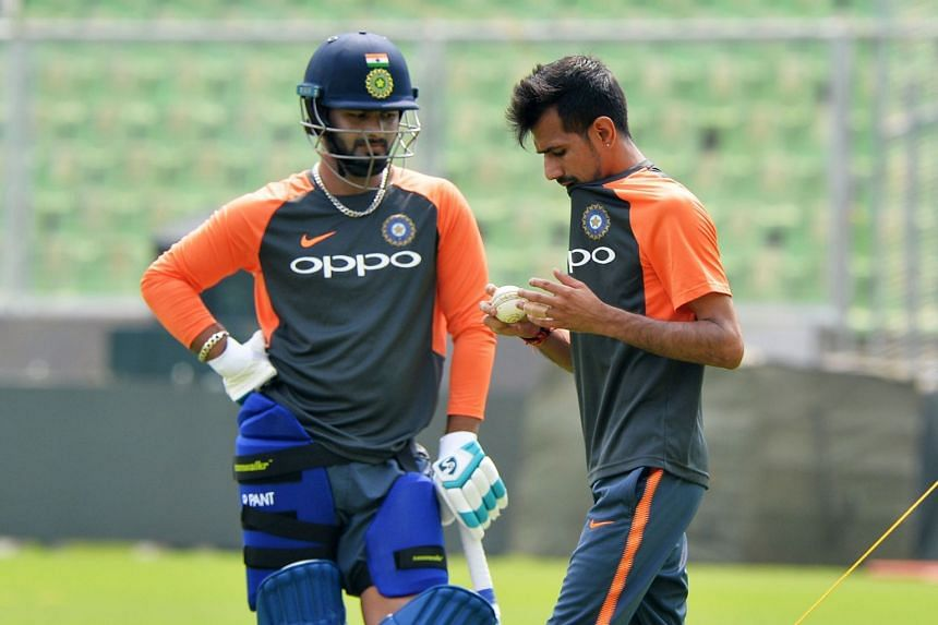 Indian bowler Yuzvendra Chahal (right) prepares to bowl in the nets while his teammate and batsman Ambati Rayudu looks on during their team's practice session at the Greenfield International Stadium in Thiruvananthapuram, India, on Oct 31, 2018.