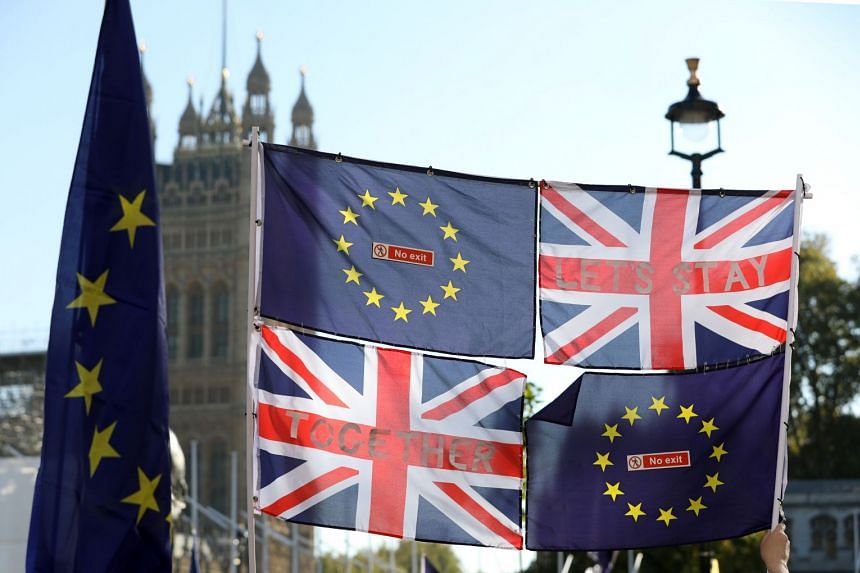 British and European Union flags fly in front of the Houses of Parliament in London.