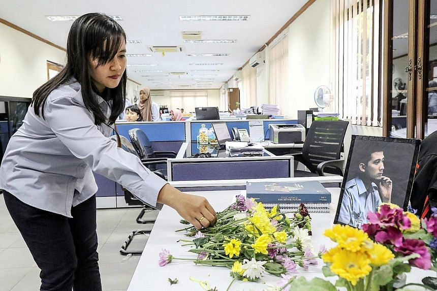 An employee of state tin miner PT Timah placing a flower on the desk of a colleague who was on the ill-fated Lion Air flight, in Pangkal Pinang, in the Bangka Belitung islands, on Wednesday. Four staff of PT Timah and three employees of a Timah subsi