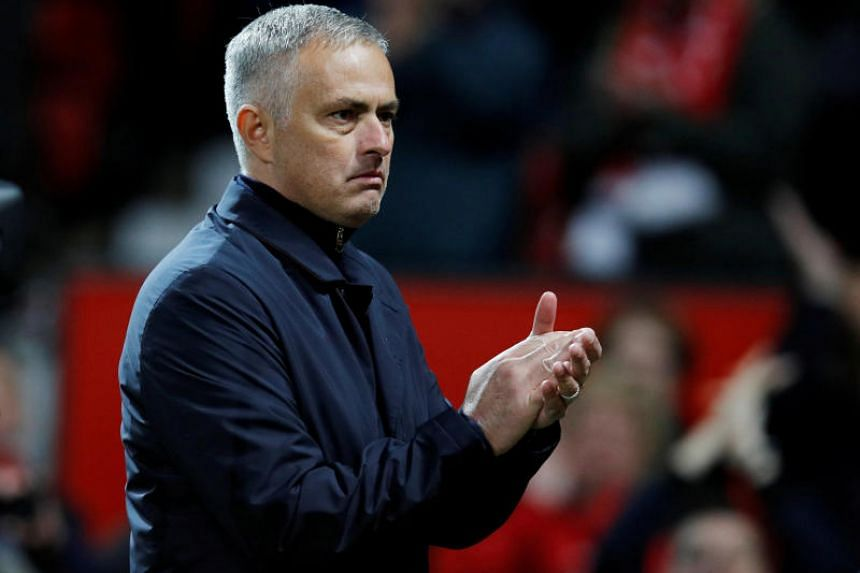 Manchester United manager Jose Mourinho applauds fans at the end of a match.