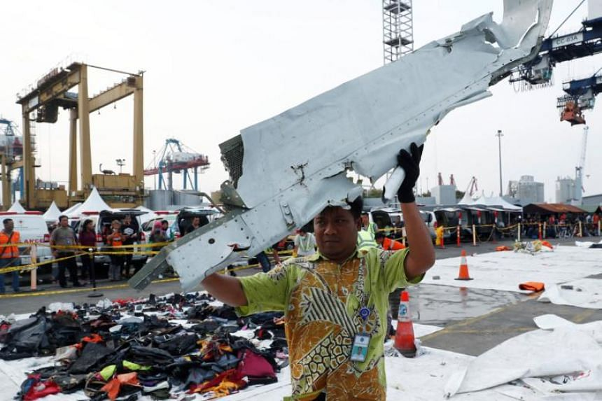 A worker holds up recovered debris believed to be from Lion Air flight JT 610 at Tanjung Priok port in Jakarta, Indonesia, on Nov 2, 2018.