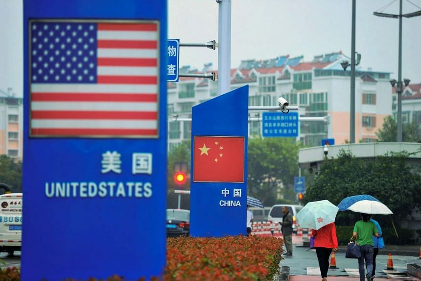 Signs with the US flag and Chinese flag are seen outside a store selling foreign goods in Qingdao, Shandong, on Sept 19, 2018.