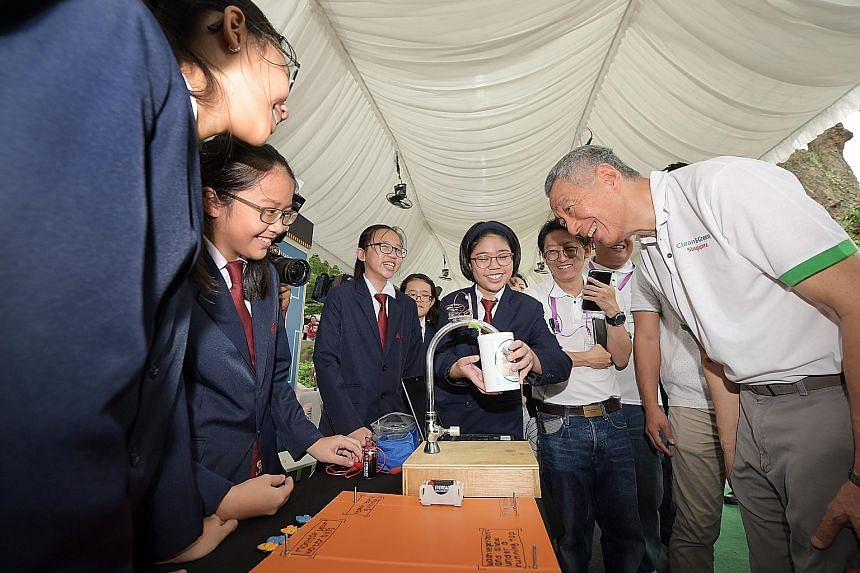 Students from Nan Chiau High School showing Prime Minister Lee Hsien Loong their project, which uses a water sensor installed at the tap to help users save water, at the Clean and Green Singapore carnival at Wisma Geylang Serai yesterday.