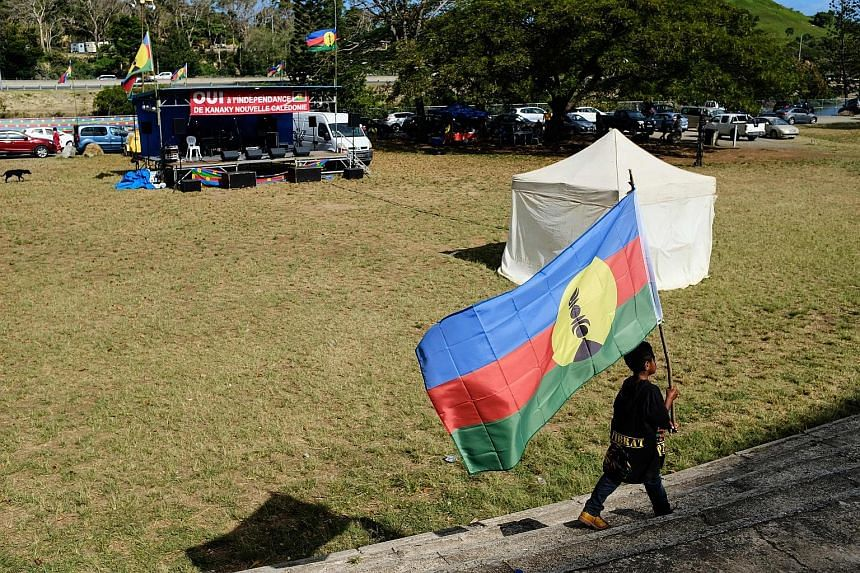 """A boy with the flag of the Kanak and Socialist National Liberation Front (FLNKS) during a meeting of the FLNKS campaign for a """"yes"""" to New Caledonia's independence from France, in Noumea, on New Caledonia, last Tuesday."""