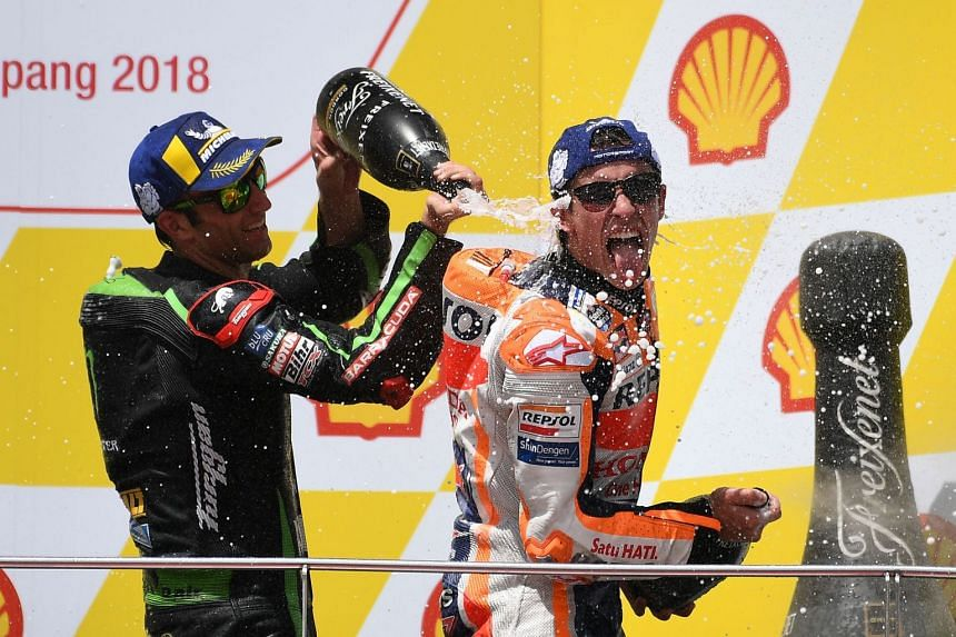 Honda's Marc Marquez (right) celebrates on the podium with Yamaha's Johann Zarco after winning the Malaysia MotoGP at the Sepang International Circuit on Nov 4, 2018.