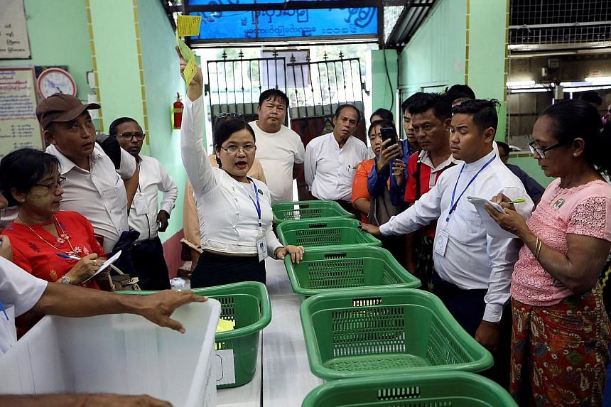 A Union Election Commission staff member counting votes at a polling station in Yangon.