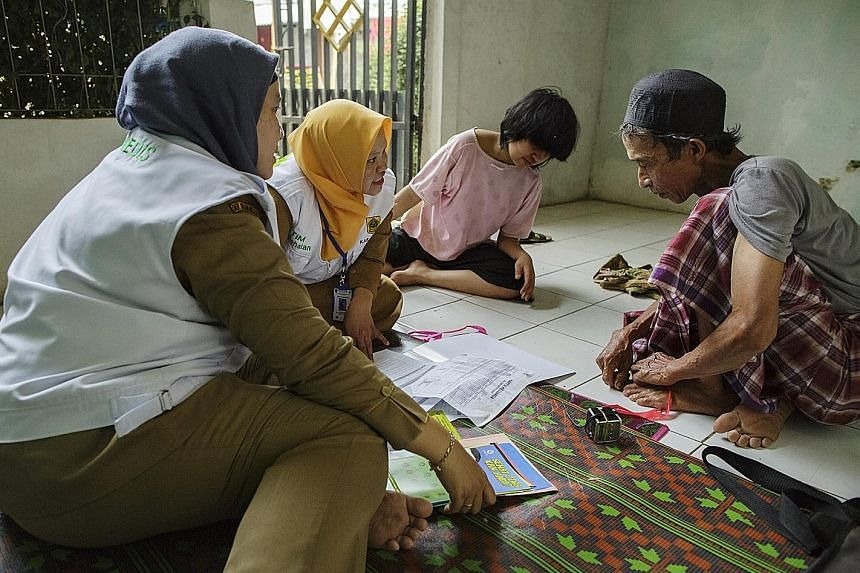 Community health workers chatting    with residents of Banjarsari village as part of government efforts on mental health. Over 7,000 medical workers across Indonesia have been trained to deal with people with mental health issues.