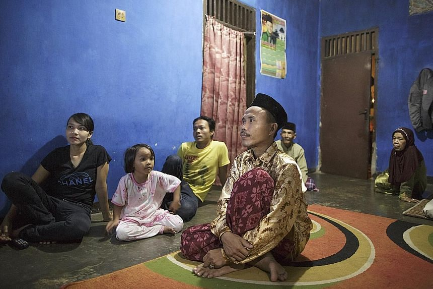 Mr Sodikin, 34, who had been confined to a shed for more than eight years, watching television with his family. When he was rescued by disability rights advocates in May 2016, he had to be carried out of the hut because his muscles had atrophied.