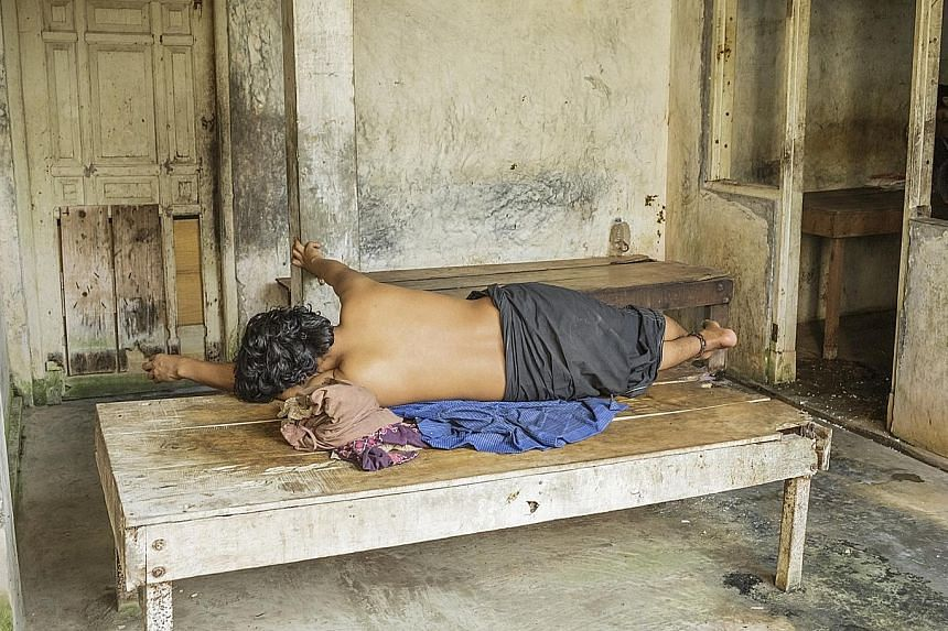 A man lies with his ankle chained to a bed at the Syamsul Ma'arif faith healing centre in Central Java. Human Rights Watch has called for regular inspection and monitoring of such centres.
