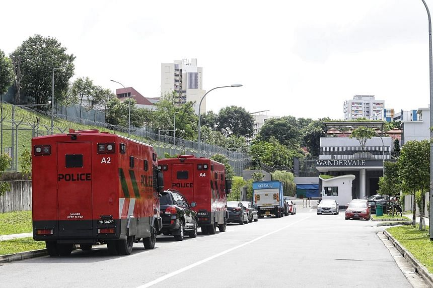 Police (above) and their vehicles (left) at the scene of the incident yesterday at Wandervale executive condominium in Choa Chu Kang. The suspect was nabbed six hours after police officers arrived at the scene.