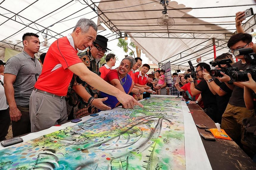 Prime Minister Lee Hsien Loong discussing the details of an artwork at a family carnival during yesterday's tree-planting event. He also opened a new sheltered linkway for residents of Fern Spring and Fern View estates.