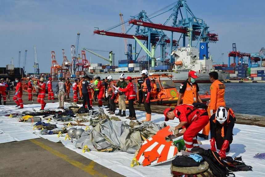 Rescue team members laying out the wreckage, which shows part of the logo of Lion Air Flight JT610 that crashed into the sea, at Tanjung Priok port in Jakarta on Oct 29, 2018.