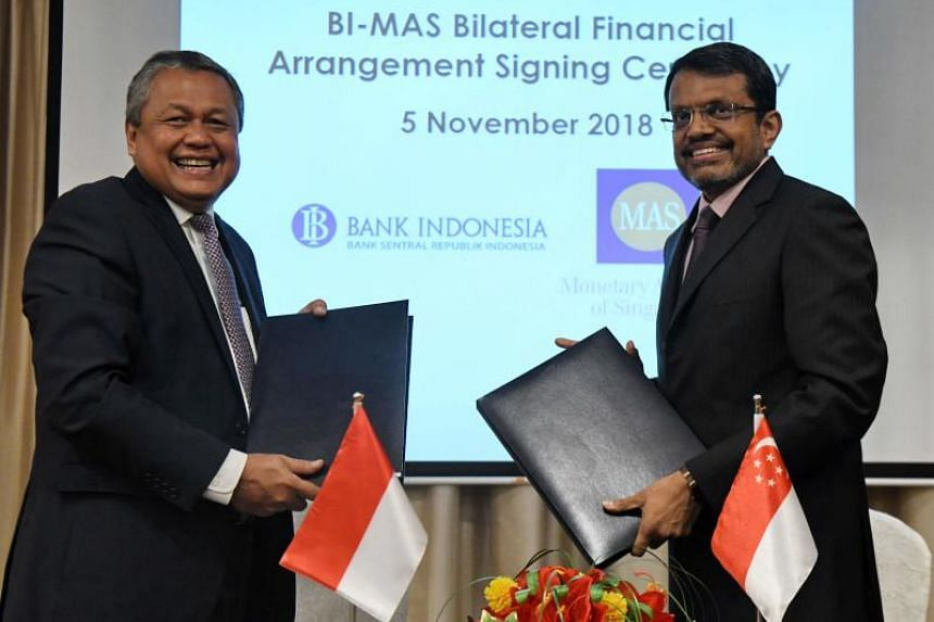 Bank Indonesia (BI) governor Perry Warjiyo (L) and Monetary Authority of Singapore (MAS) managing director Ravi Menon exchange documents after a signing ceremony for the bilateral financial agreement.