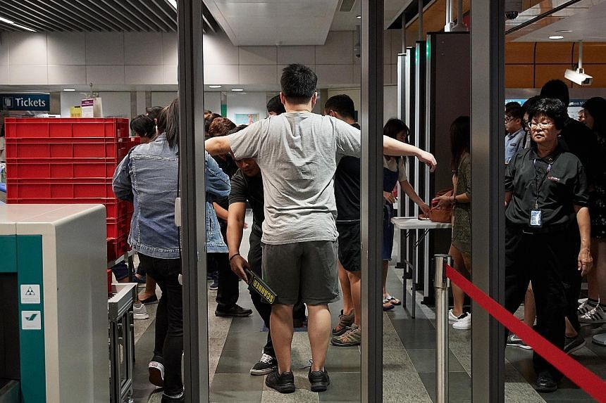 Commuters being screened during an emergency preparedness exercise at Newton MRT station in February. For its trial starting next Monday, LTA said X-ray scanners and metal detectors will be installed at selected MRT stations, and that screening equip