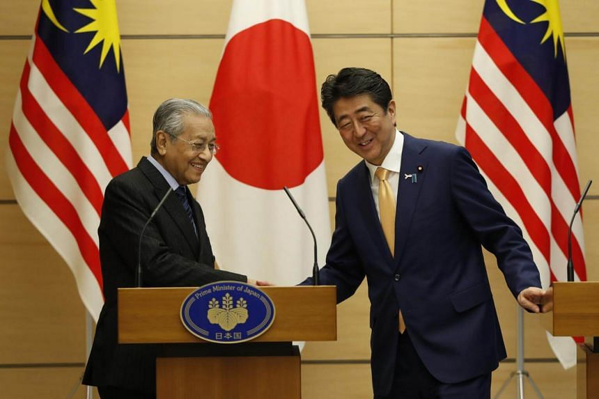 Malaysia's Prime Minister Mahathir Mohamad exchanging greetings with Japan's Prime Minister Shinzo Abe at the end of their joint news conference at Abe's official residence in Tokyo, on Nov 6, 2018.