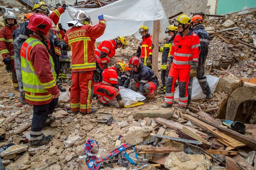 Firemen cover a body at the site where two buildings collapsed in Marseille.