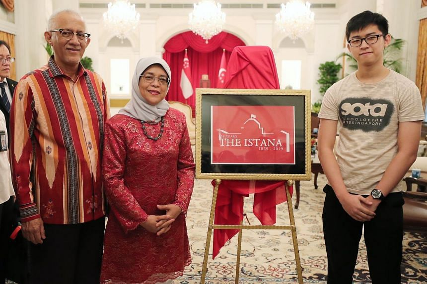 President Halimah Yacob and her husband Mohamed Abdullah Alhabshee with School of the Arts Singapore student Charlie Chua and his winning design of the Istana 150 logo.