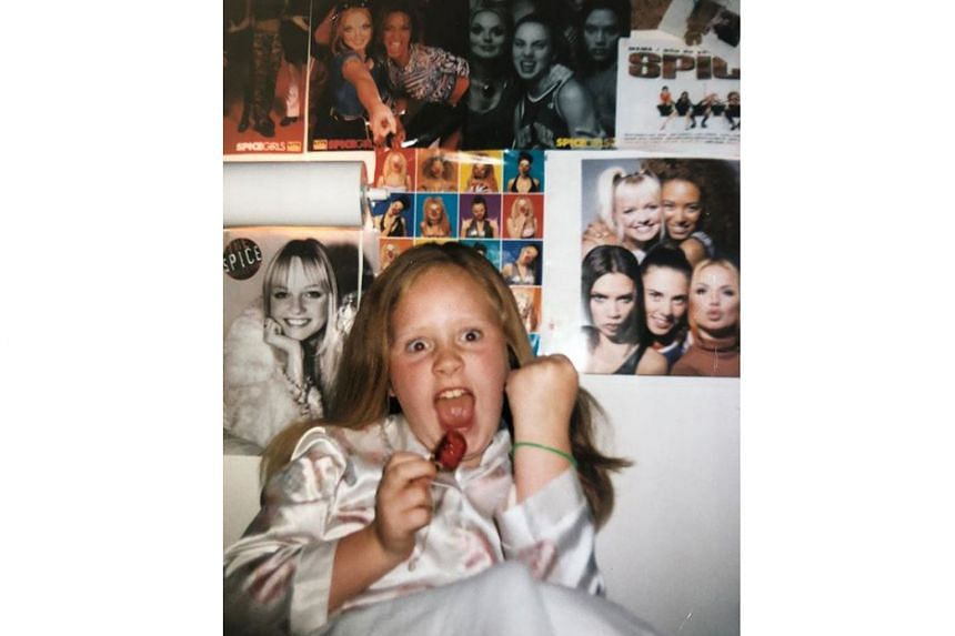 Singer Adele, in reaction to news of the Spice Girls reunion tour, posted a picture of herself (above) in her younger days with posters of the girl group.