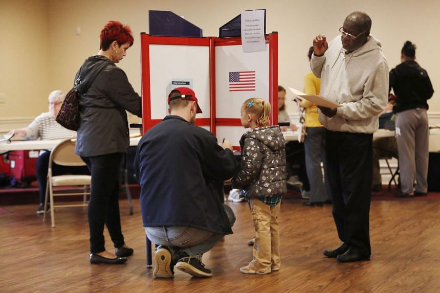 Andrew Gibson (centre, left) of Streetsboro, Ohio casts his ballot as his daughter Sophia McNeal, age four, looks on.