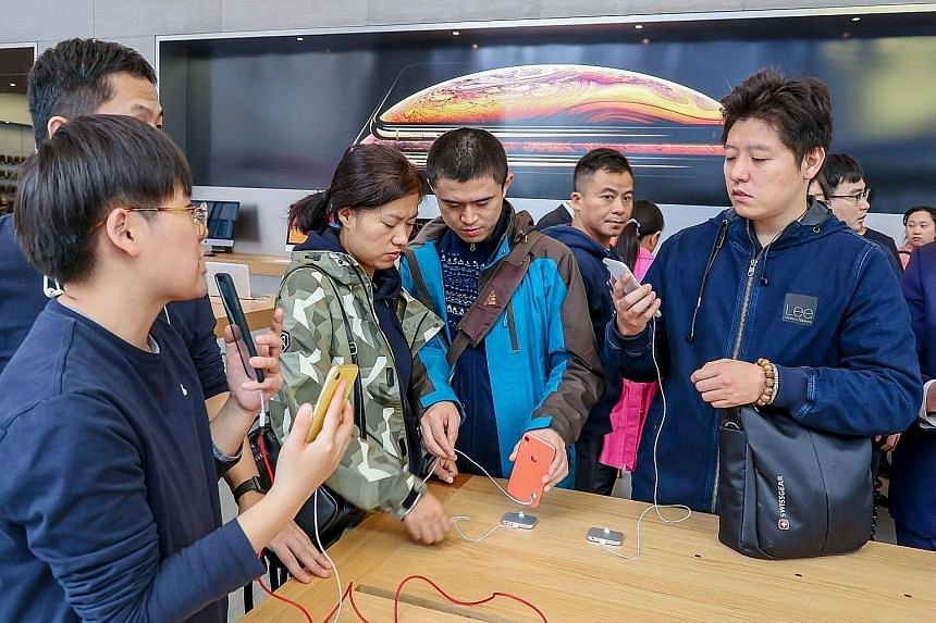 Potential buyers of the iPhone XR at an Apple store in Shanghai. Companies that supply Apple have been badly hit after a Nikkei business report said the tech firm had told Taiwan's Foxconn and Pegatron to scrap planned new production lines for the iP