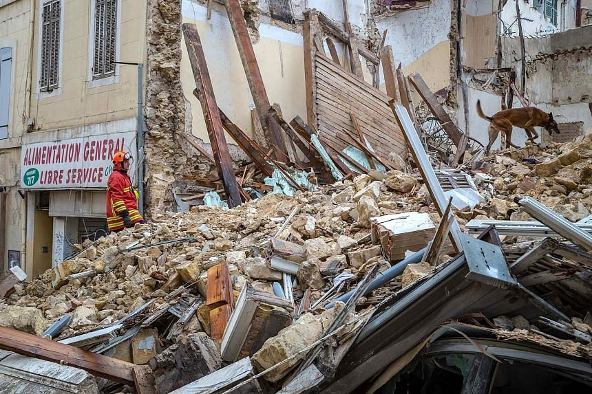 A fireman and a dog searching at the site where two buildings collapsed in Marseille, France, on Monday.
