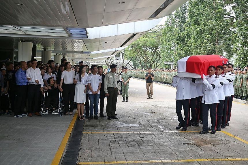 Corporal First Class (CFC) Liu Kai's father (front row, second from left), mother, and two sisters hold hands as they watch pallbearers carry his casket into the service hall at Mandai Crematorium. Hundreds of servicemen lined the driveway for the mi