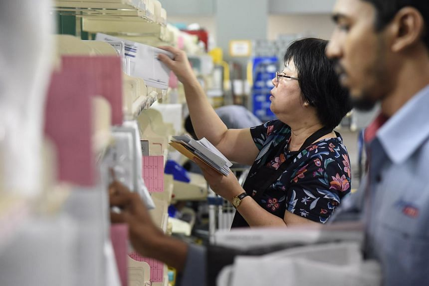 SingPost staff sorting mail items in its delivery base in Paya Lebar.