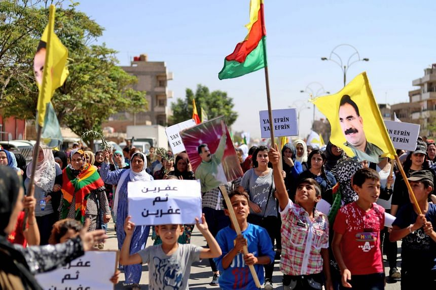 Syrian Kurds marching with Kurdish flags and flags showing a portrait of PKK leader Abdullah Ocalan, in a September 2018 protest.