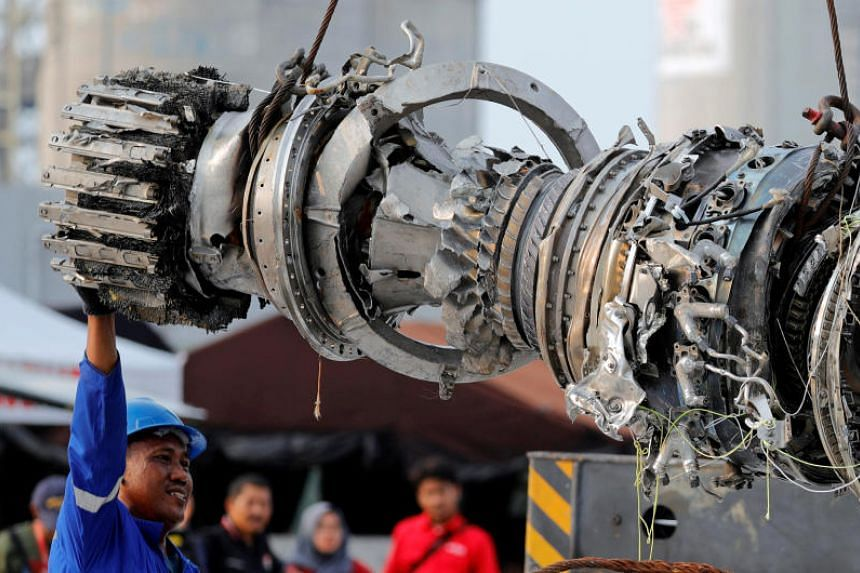Workers lift a turbine engine of the Lion Air flight JT610 jet, at Tanjung Priok port in Jakarta, Indonesia, on Nov 4, 2018.