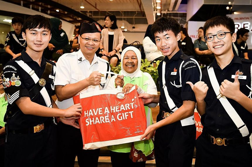 Boys' Brigade members (from left) Isaac Tan, Caleb Tan and Too Bowen, all 15, with Mr Poh Leong Berg, president of The Boy's Brigade Singapore, and Madam Habibi Rosdi.