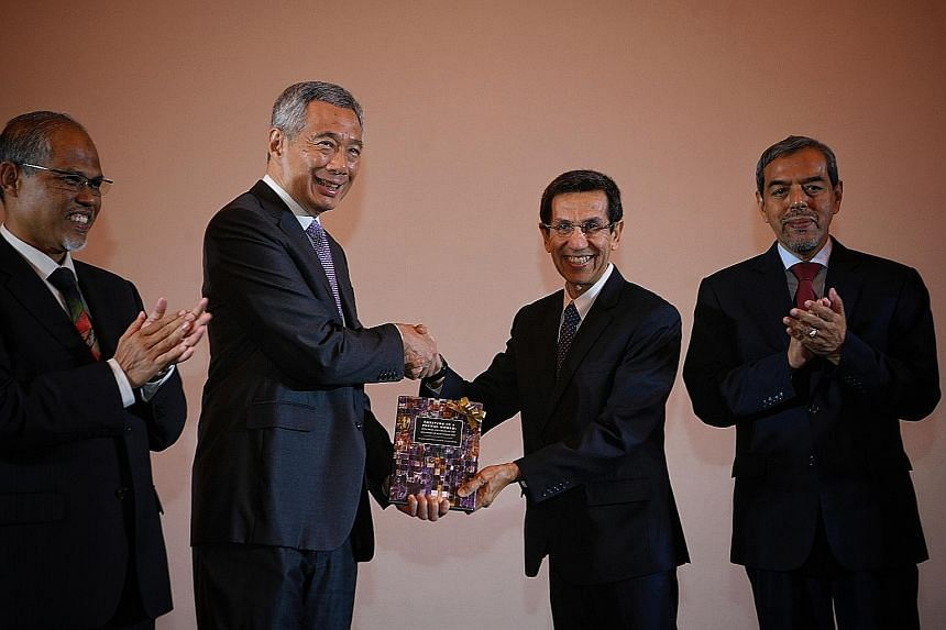 Prime Minister Lee Hsien Loong receiving a copy of the book Thriving In A Plural World: Principles And Values Of The Singapore Muslim Community from Muis president Mohammad Alami Musa at the conference to mark Muis' 50th anniversary yesterday. With t