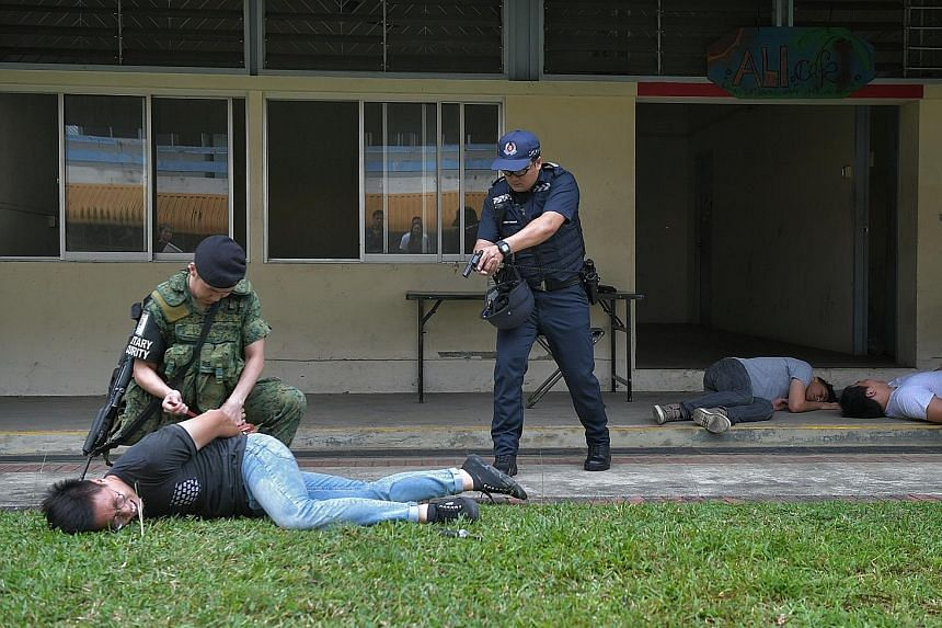 In this training scenario, a police officer and an SAF soldier on a routine patrol arrest a suspect after they were alerted to a knife attack at a cafe.
