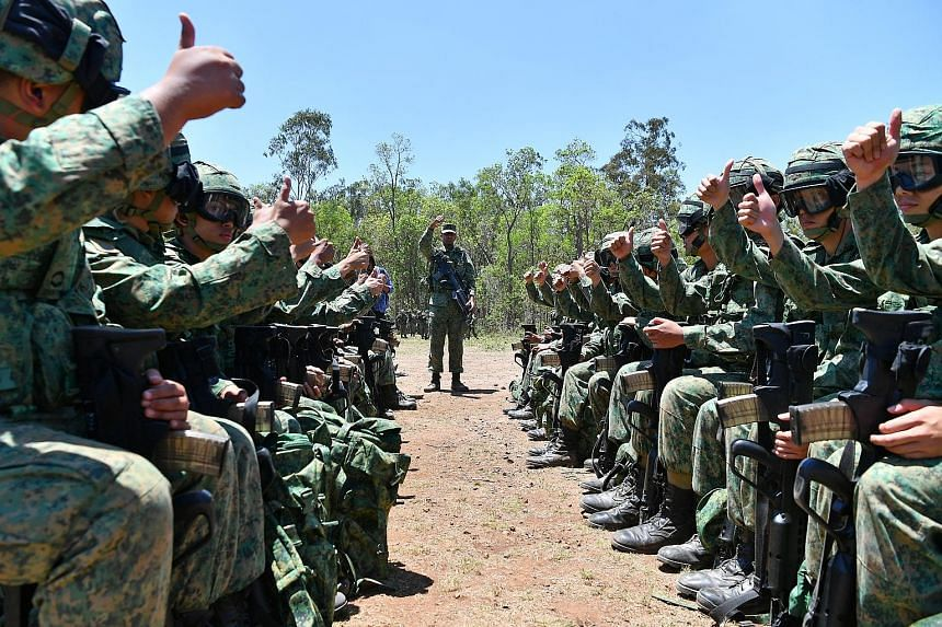 """Soldiers from 1st Guards Battalion give a thumbs-up sign after they board a mock-up of a helicopter as part of their rehearsals on the procedures to follow when boarding and disembarking. Captain (Dr) Jeriel Tan (at left) and medics attend to a """"casu"""