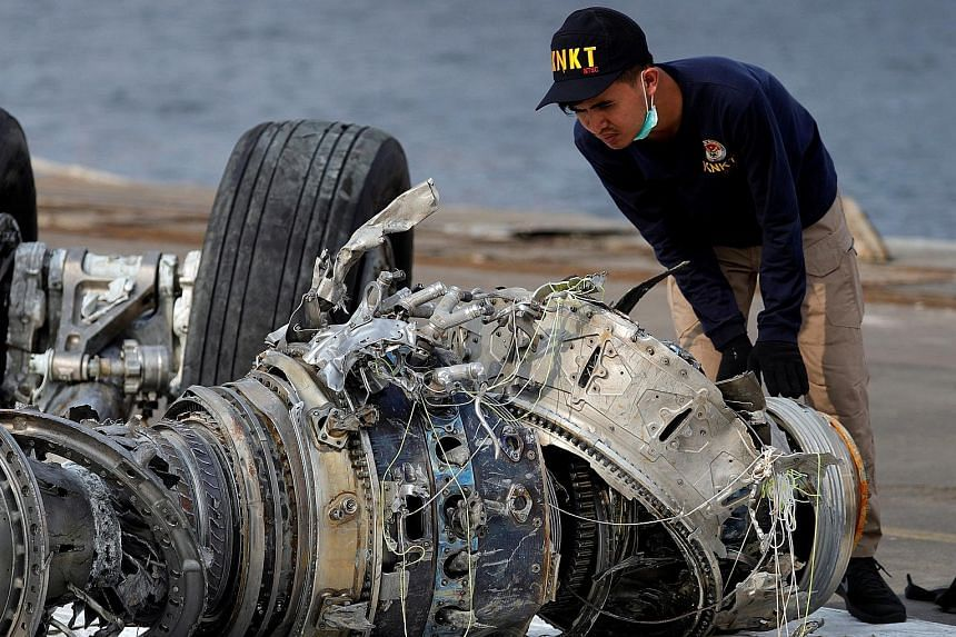 An Indonesian official examining a turbine engine from the crashed Lion Air jet at Tanjung Priok port in Jakarta on Sunday. The plane crashed on Oct 29 en route to Pangkal Pinang from Jakarta, killing all 189 people on board.