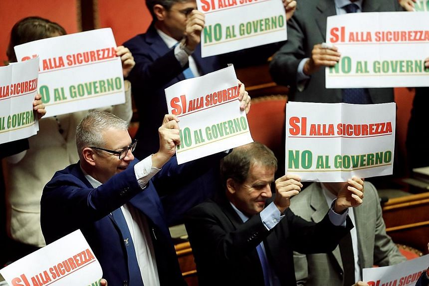 """Opposition senators showing their objections to the decree by holding placards that say, """"Yes to safety, no to the government"""", before the confidence vote was held by the Senate in Rome."""