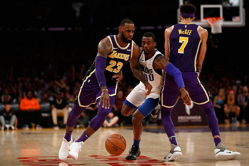 LeBron James dribbles off the screen of JaVale McGee of the Los Angeles Lakers as Harrison Barnes of the Dallas Mavericks defends during the second half of a game at Staples Center in Los Angeles, California, on Oct 31, 2018.