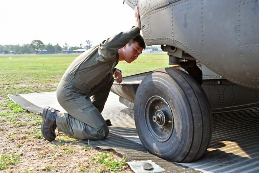 An RSAF personnel checks the wheels as part of the procedure to ready the Chinook for flight at Warriors Camp in this year's Exercise Wallaby.
