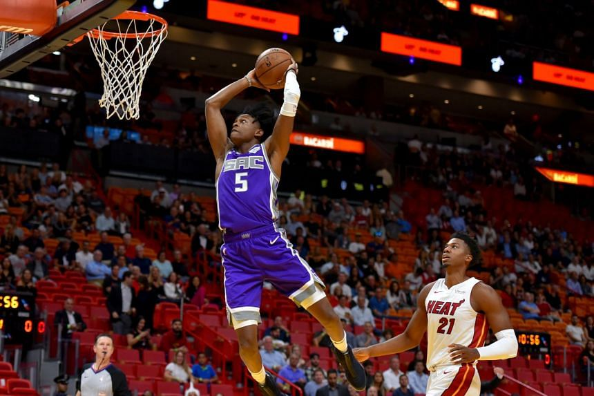 Sacramento Kings guard De'Aaron Fox dunks the ball past Miami Heat center Hassan Whiteside during the first half at American Airlines Arena, on Oct 30, 2018.