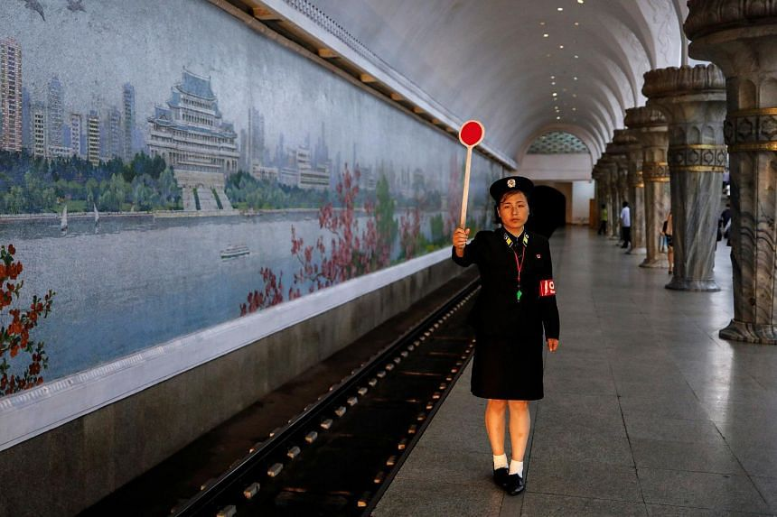 A railway worker gives a signal as the train leaves a train station in Pyongyang, North Korea.