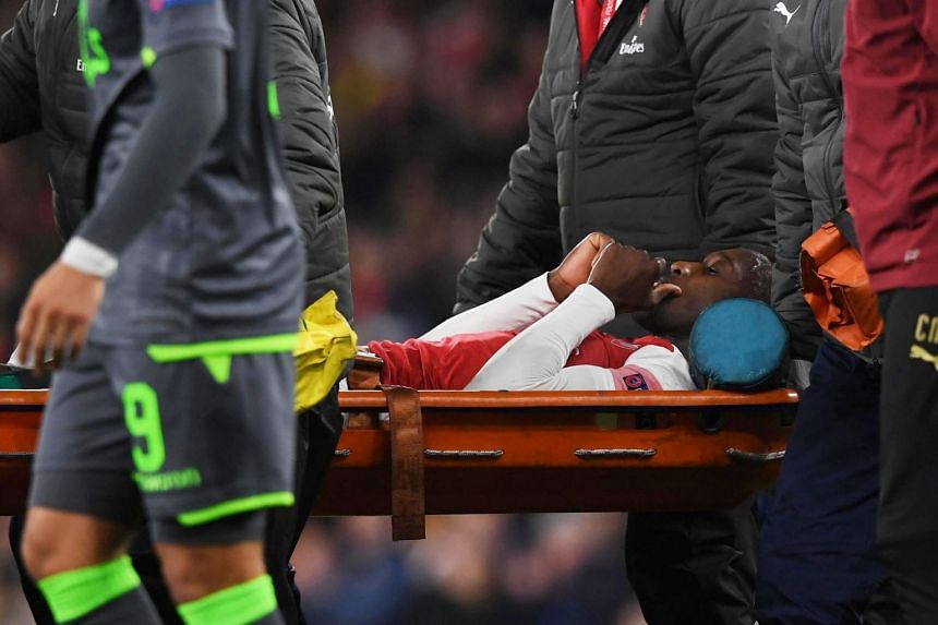 Arsenal's Danny Welbeck is carried off the pitch.