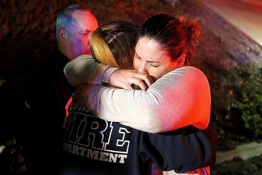 People comforting each other after a mass shooting at a bar in Thousand Oaks, California, yesterday.