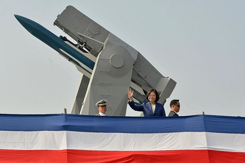 Taiwanese President Tsai Ing-wen waving from the deck of the frigate Ming Chuan during a ceremony to commission two Perry-class guided missile frigates from the United States yesterday.